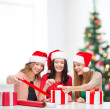 Smiling women in santa helper hats with gift boxes — Stockfoto #34924291