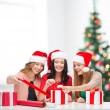 Smiling women in santa helper hats with gift boxes — Stok fotoğraf