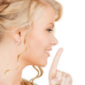 Woman with finger on her lips — Stockfoto