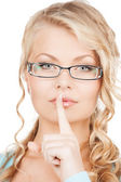 Woman wearing eyeglasses with finger on her lips — Stock Photo