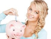 Woman puts cash money into big piggy bank — Stock Photo