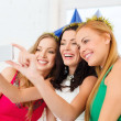 Three smiling women in hats having fun with camera — Stock Photo #35014289