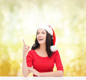 Woman in santa helper hat pointing to something — Stock Photo