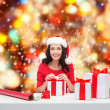 Woman in santa helper hat with many gift boxes — Foto Stock