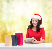 Smiling woman with shopping bags and tablet pc — Stock Photo