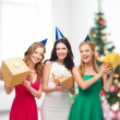 Three smiling women in blue hats with gift boxes — Stockfoto