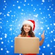 Smiling woman in santa helper hat with parcel box — Stockfoto