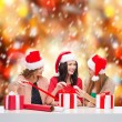 Smiling women in santa helper hats with gift boxes — Stockfoto #35272513