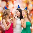 Three smiling women in hats blowing favor horns — Stock Photo #35272563