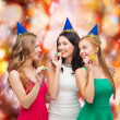 Three smiling women in hats blowing favor horns — Foto de Stock