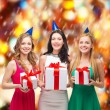 Three smiling women in blue hats with gift boxes — ストック写真 #35272599