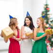 Three smiling women in blue hats with gift boxes — Stock Photo