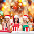 Stock Photo: Smiling women in santhelper hats with gift boxes