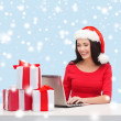 Woman with gift boxes and laptop computer — Foto Stock