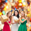 Three smiling women in blue hats with gift boxes — Stock Photo #35273695