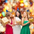 Three smiling women in blue hats with gift boxes — Stok fotoğraf
