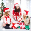 Women in santa helper hats with many gift boxes — Stock Photo