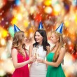 Three women wearing hats with champagne glasses — Foto de Stock