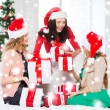 Women in santa helper hats with many gift boxes — Foto de Stock