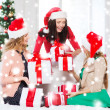 Women in santa helper hats with many gift boxes — Stok fotoğraf