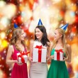 Three smiling women in blue hats with gift boxes — Stock Photo #35275341