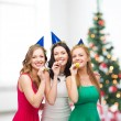 Three smiling women in hats blowing favor horns — Stockfoto