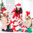 Women in santa helper hats with many gift boxes — Stock Photo #35276503