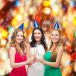 Three women wearing hats with champagne glasses — Stock Photo #35276569