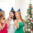 Three smiling women in hats blowing favor horns — Stock Photo