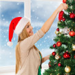 Woman in santa helper hats decorating a tree — Photo