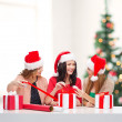 Smiling women in santa helper hats with gift boxes — Stock Photo #35277391