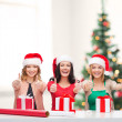 Smiling women in santa helper hats with gift boxes — Stock Photo #35277753