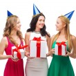 Three smiling women in blue hats with gift boxes — Foto Stock