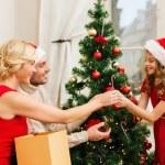 Smiling family decorating christmas tree — Stock Photo