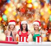 Santa yardımcı şapka hediye kutuları gülümseyen kadın — Stok fotoğraf
