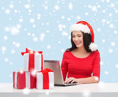 Woman with gift boxes and laptop computer — Stock Photo
