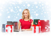 Woman with gift boxes, bags and laptop computer — Stock Photo