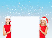 Women in santa helper hats with blank white board — Stock Photo