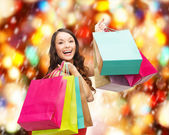 Woman in red dress with colorful shopping bags — Stock Photo