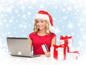 Woman with gifts, laptop computer and credit card — Stock Photo