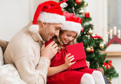 Smiling father and daughter opening gift box — Stockfoto