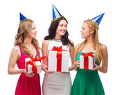 Three smiling women in blue hats with gift boxes — Photo
