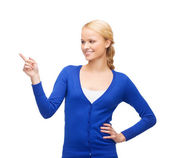 Smiling woman in pointing her finger — Stock Photo