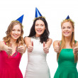 Three women wearing hats and showing thumbs up — Stock Photo #35281077