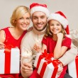 Smiling family holding gift boxes and sparkles — Stock Photo #35281401
