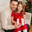 Stock Photo: Smiling father and daughter holding gift box