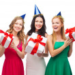 Three smiling women in blue hats with gift boxes — Stock Photo #35281647