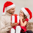 Stock Photo: Smiling father giving daughter gift box