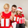 Stock Photo: Happy family opening gift boxes