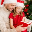 Smiling father and daughter reading book — Stock Photo